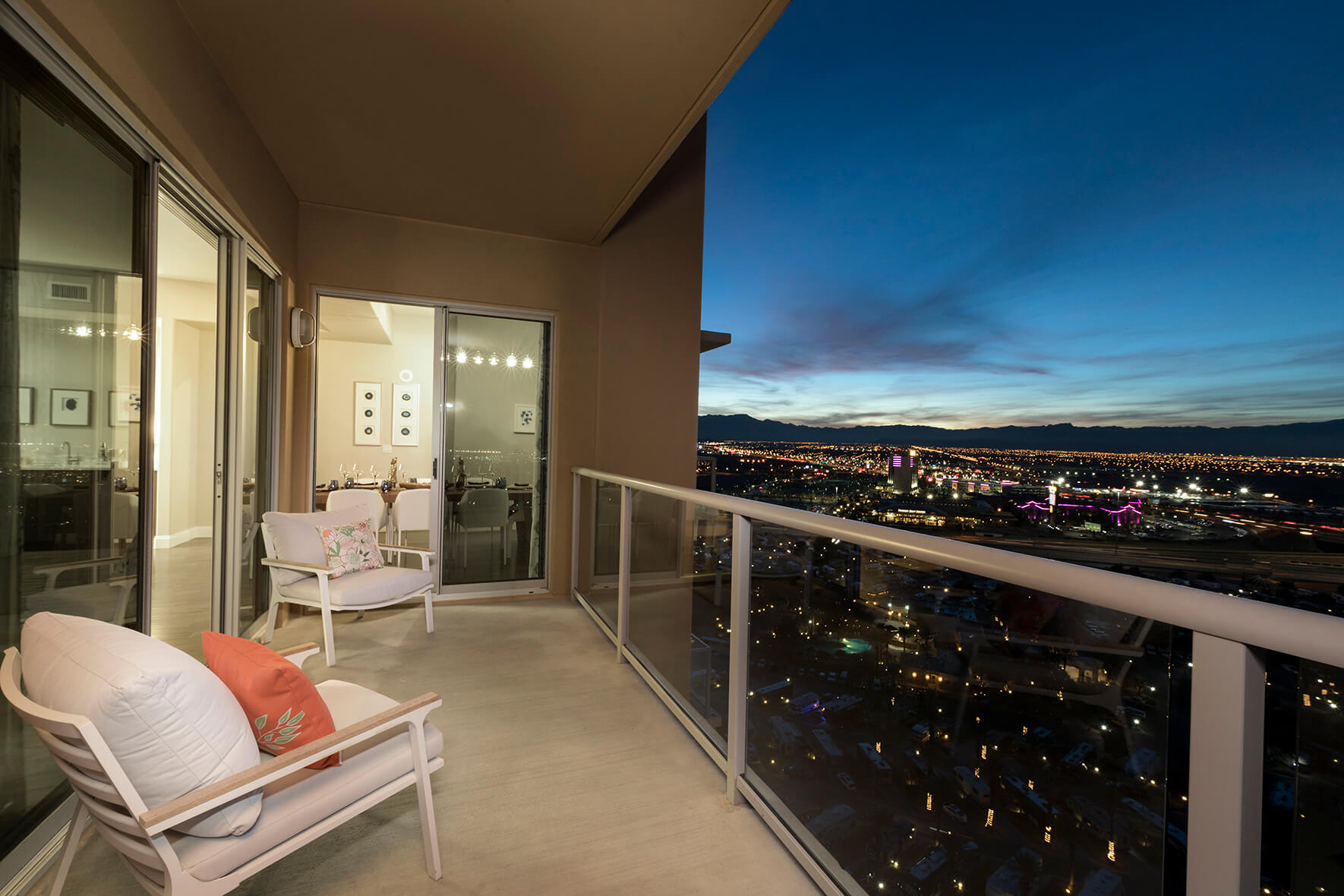 a balcony with two white chairs at night looks out over las vegas territory