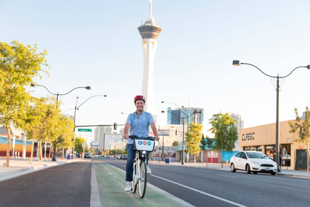 Male riding bike on street with Stratosphere tower in background