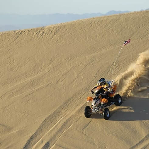 atv with driver races down sand dune in sun