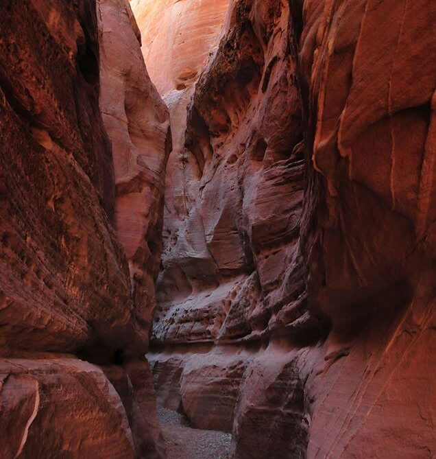 valley of fire red rocks with path surrounding by high rock cliffs on either side
