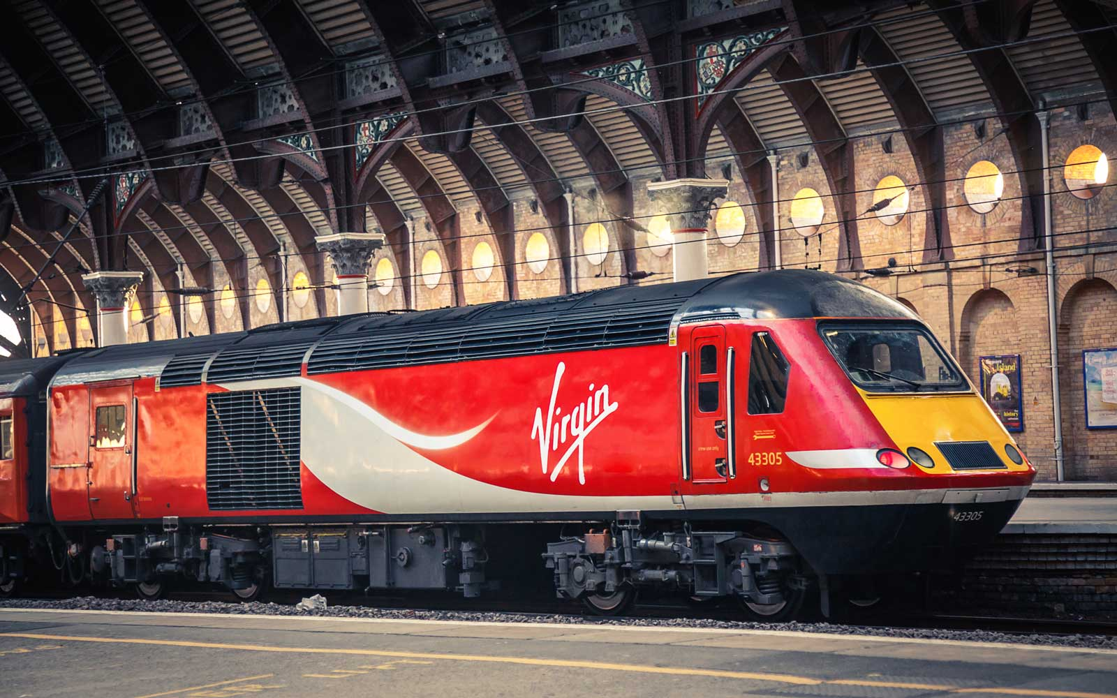 red virgin train pulls into covered station