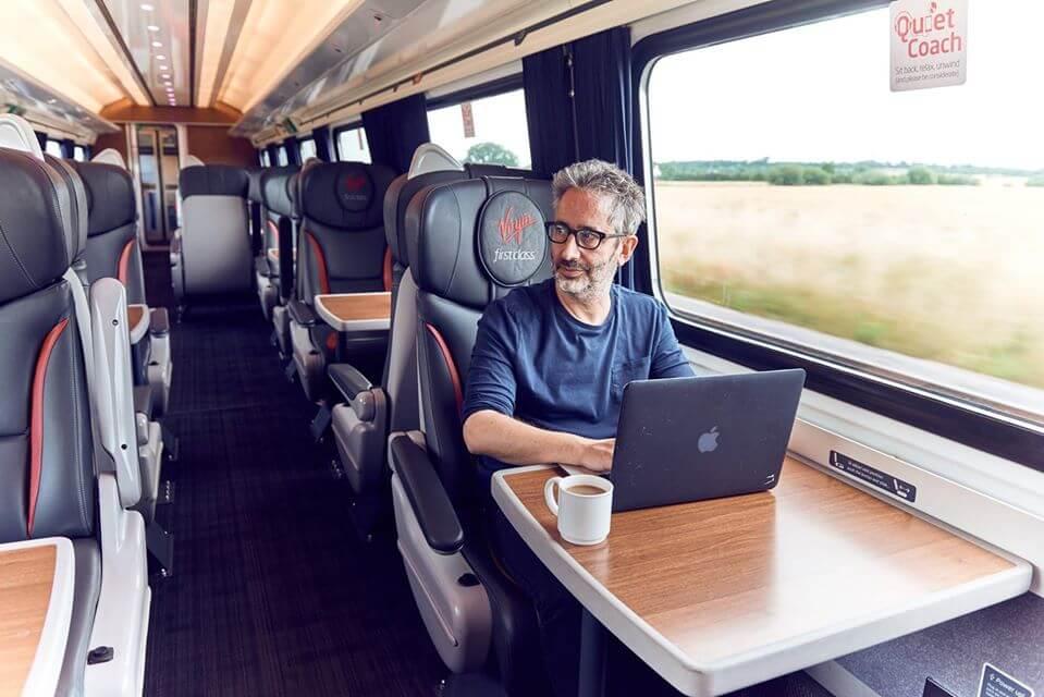 Pssennger onboard virgin trains uses entertainment system via laptop