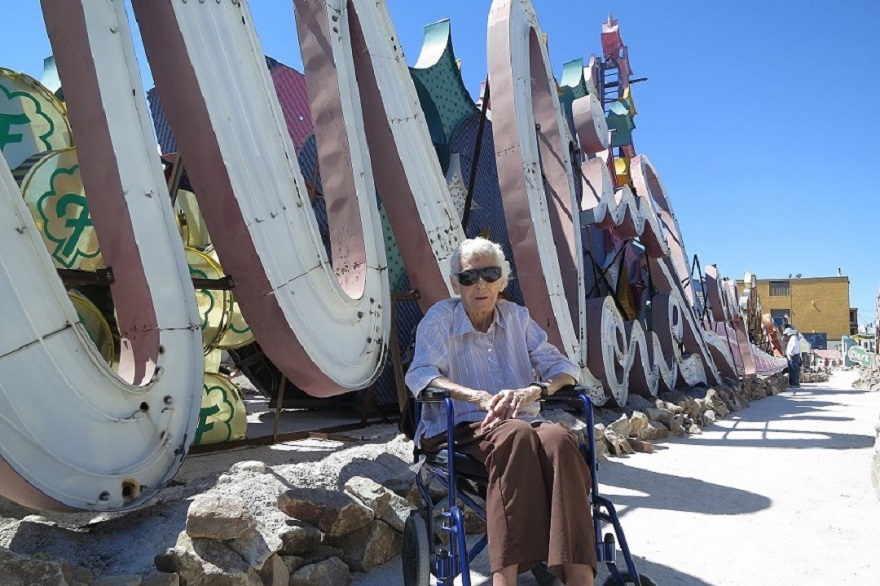 woman in wheelchair sits infront of neon sign installation