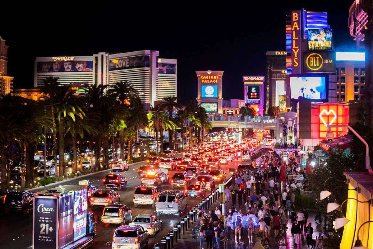 the las vegas stip at night with heavy traffic and pedestrians