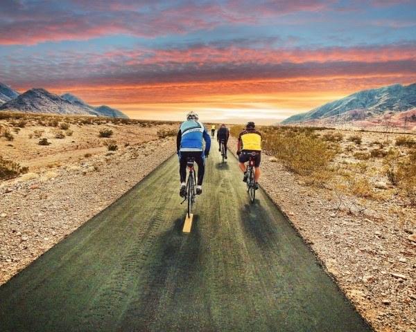 cyclists bike through desert road