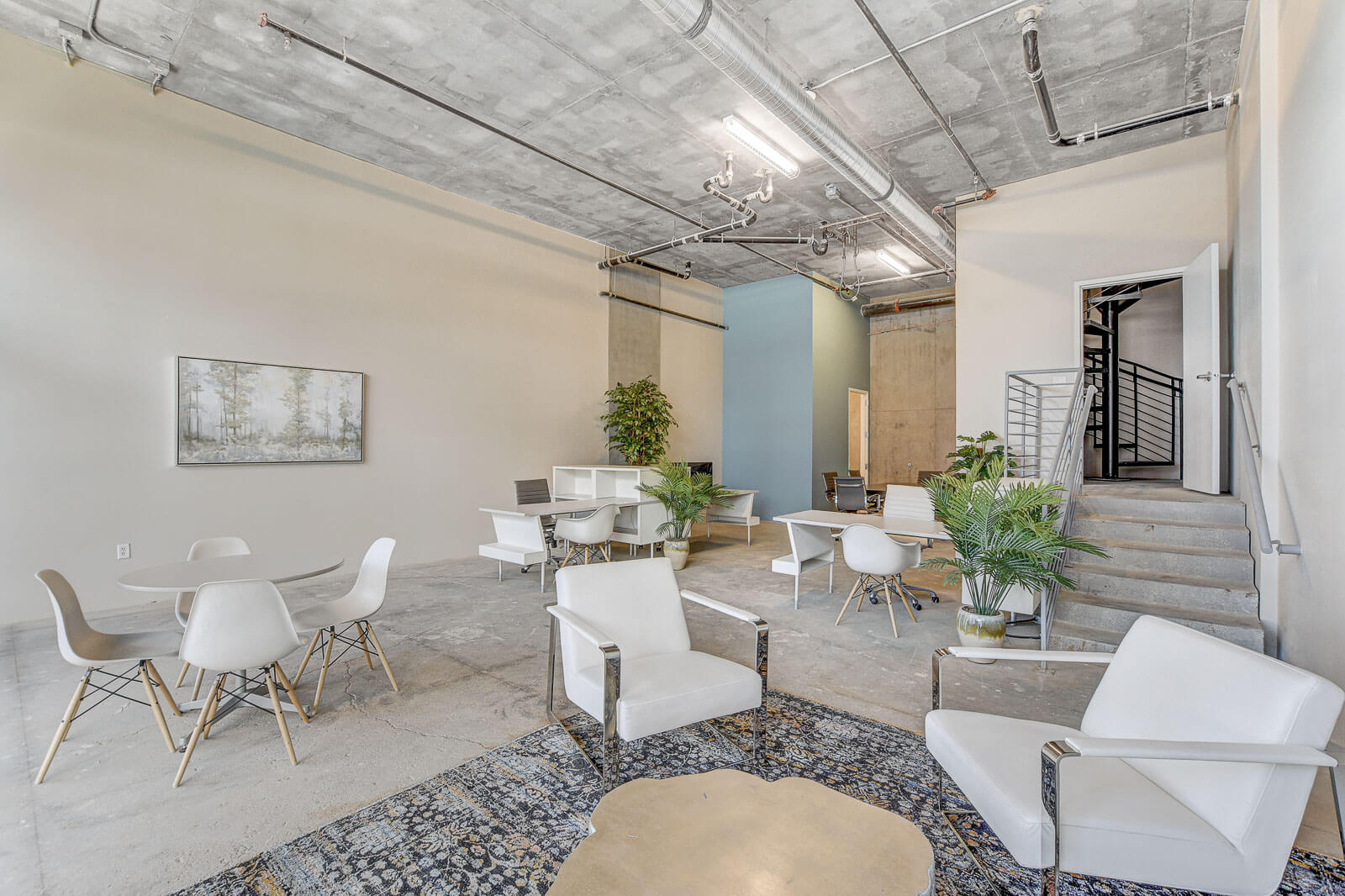 interior shot of a downstairs workspace at Juhl with a variety of tables and white chairs