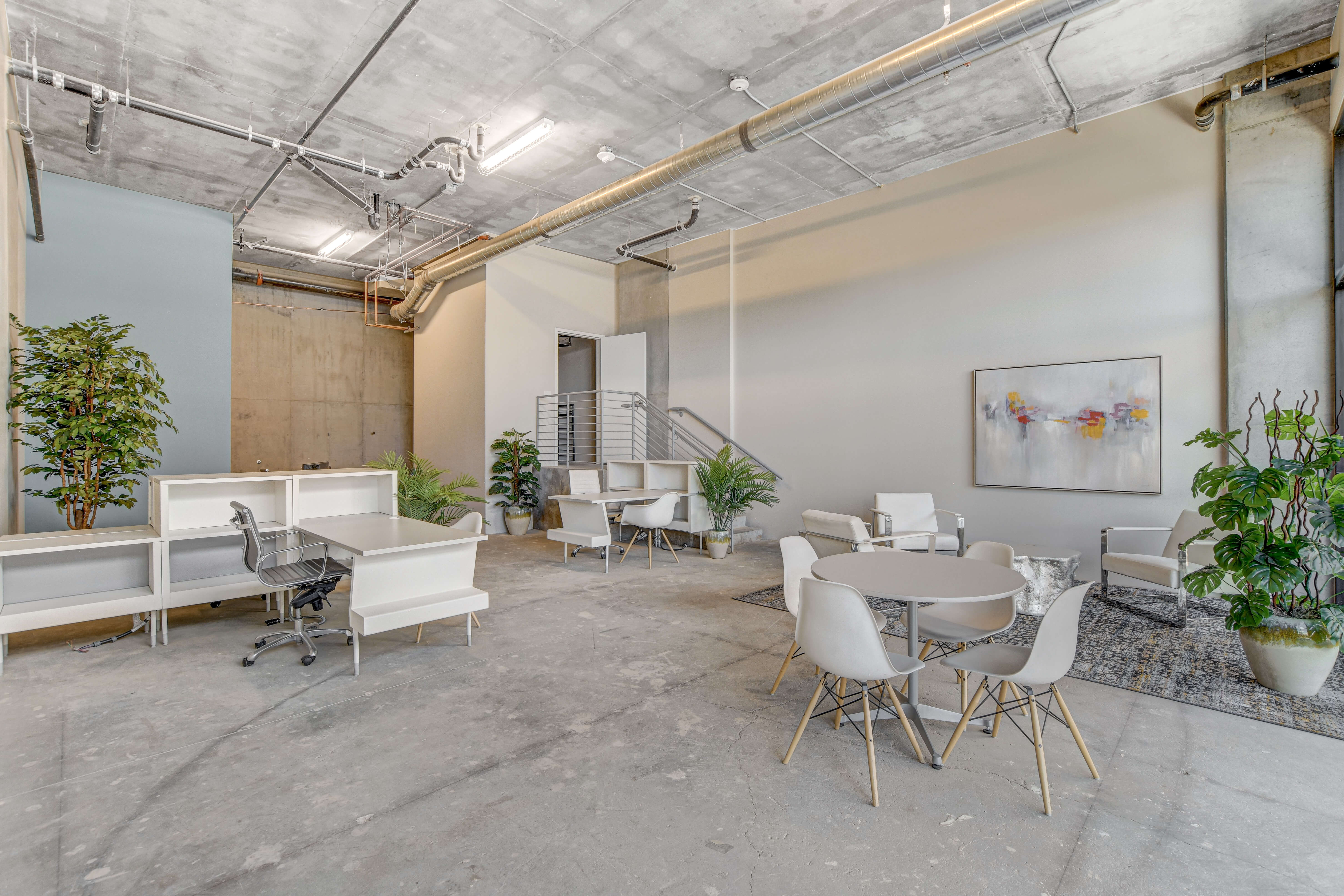 alternate shot of a downstairs workspace at Juhl with a variety of tables and white chairs
